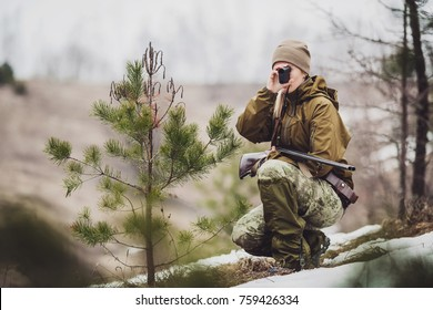 female hunter ready to hunt, holding laser finder in forest. hunting and people concept