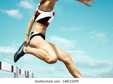Female hurdle runner leaping over the hurdle