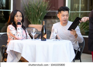 Female hustler on a date with a gullible man paying for her restaurant bill in an outdoor cafe.  The image depicts gentleman or foolish generosity in a dating scenario.