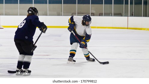 Female ice hockey players shoots the puck during a game