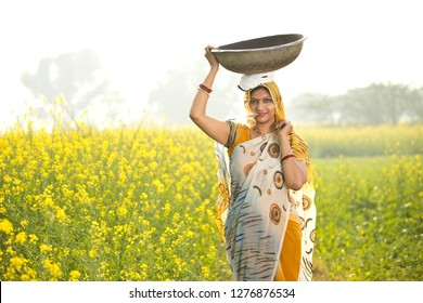 Female Indian farmer carrying iron pan on head in agriculture field