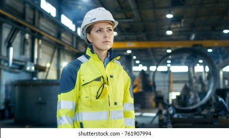 Female Industrial Worker in the Hard Hat Standing in a Middle of a Heavy Industry Manufacturing Factory. In the Background Various Metalwork Components are Seen.