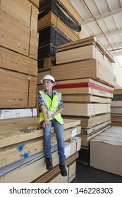 Female industrial worker having coffee while sitting on stack of wooden planks