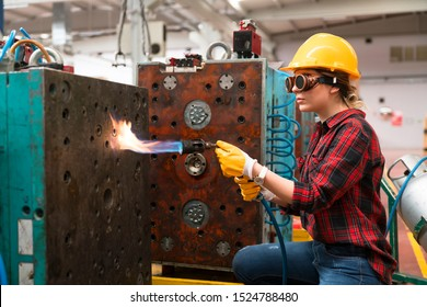 Female industrial worker working with blow torch in factory