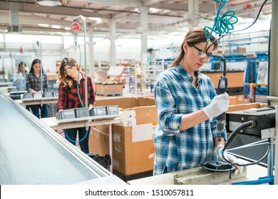 Female industry employees work on production line at factory