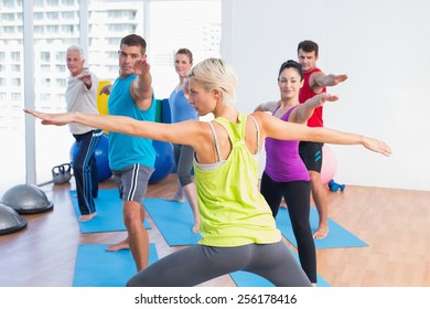 Female instructor with class practicing warrior pose in fitness club