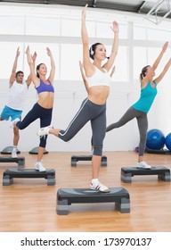 Female instructor with fitness class performing step aerobics exercise in gym