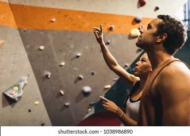 Female instructor giving instructions to a man on wall climbing. Man learning the art of rock climbing at an indoor climbing centre.