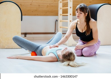 Female instructor helping for client doing self-massage technique applying special balls for back pain relief, working out lying on floor at pilates studio.Correct posture maintaining body concept.