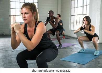 Female instructor leads boot camp class in power yoga pose high intensity cardio unisex coed team