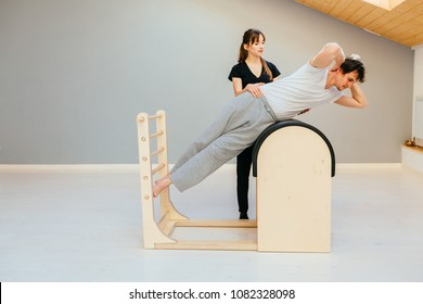 Female instructor of pilates helping to young man workout on barrel.
