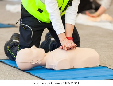 Female instructor showing CPR on training doll.
