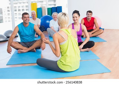 Female instructor talking with class in fitness club