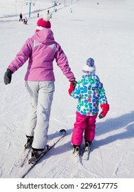 Female instructors teach a child skiing on winter resort