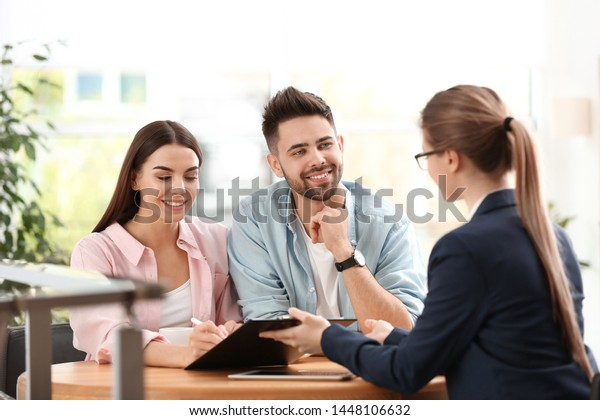 Female insurance agent working with young couple in office