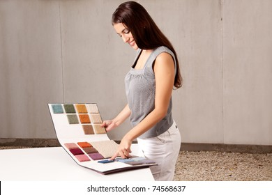 A female interior architect or designer looking at rug samples from a catalogue