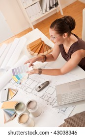 Female interior designer with color swatches and laptop at office