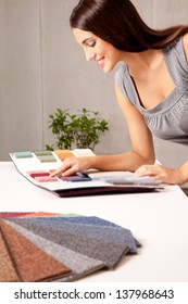 A female interior designer looking at rug samples from a catalogue