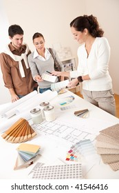 Female interior designer with two clients at office choosing colors