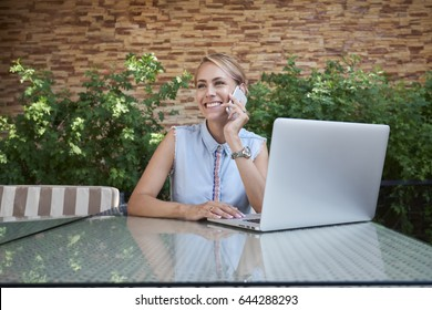 female international student talking on the phone and checking email in computer While sitting in a cafe