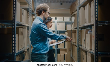 Female Inventory Manage and Storage Worker, Check Stock and Have Discussion at Work. In the Background Rows of Shelves Full of Parcels with Products Ready for a Shipment.