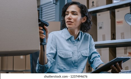 Female Inventory Manager Scans Cardboard Box and Digital Tablet with Barcode Scanner, Worker Holds Package. In the Background Rows of Cardboard Boxes with Products Ready For Shipment.