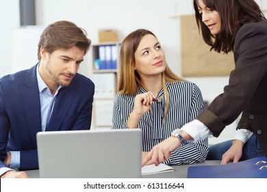 Female investment broker assisting clients as she perches on her desk discussing a presentation on her laptop with a young married couple