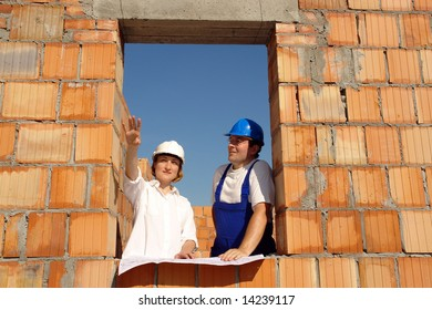 Female investor showing the site manager her house concept standing inside unfinished brick house window opening