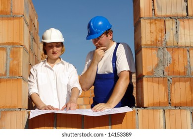 Female investor and site manager discussing building plans inside unfinished house