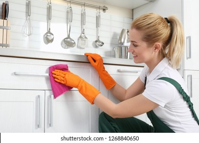 Female janitor cleaning cabinet with rag in kitchen