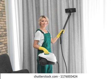 Female janitor removing dust from curtain with steam cleaner indoors