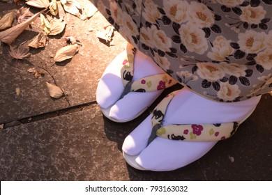 A female Japanese woman's feet in kimono in autumn.