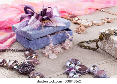 Female jewelry and gift decorative box on linen tablecloth