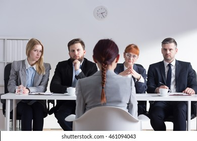 Female job applicant sitting in front of the Selection Committee. Recruiters listening intently to her speech
