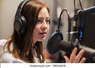 Female Jockey Talking On Microphone In Radio Studio