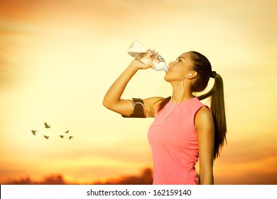 Female jogger drinking water outdoor