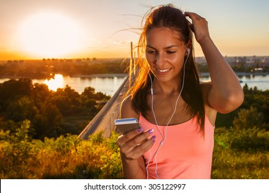 Female jogger running and listening to music on her smart phone.Sunset and lens flare effect.