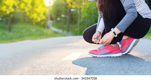 Female jogger tying her shoes preparing for a run