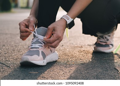 Female jogger tying shoes before running outdoors