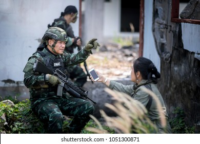 Female journalist interview soldier during war conflict. Photojournalist  work on grass field concept.
