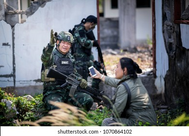 Female journalist interview soldier during war conflict. Photojournalist  work on gress field concept.