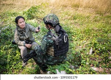Female journalist interview soldier during war conflict. Photojournalist  work on gress field concept.