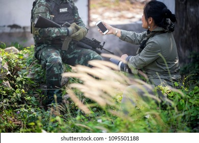 Female journalist interview soldier during war conflict. Photojournalist  work on gress field concept. selective focus at smartphone.