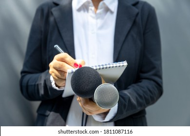 Female journalist at media event or press conference, writing notes, holding microphone. Journalism concept.