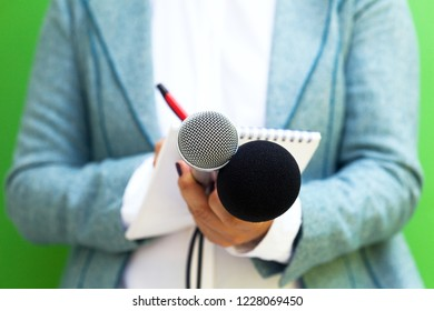 Female journalist at news conference, writing notes, holding microphone