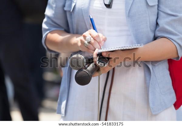 Periodista que toma notas en la conferencia de prensa