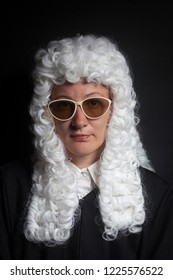 Female judge wearing a wig and black mantle with sunglasses isolated on black background