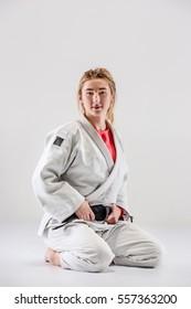 The female judokas fighter posing on gray