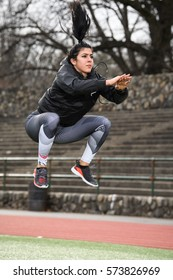 Female jumping at track doing burpees