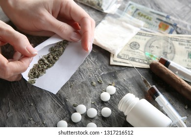 Female junkie making cigarette with marijuana on grey table. Concept of addiction